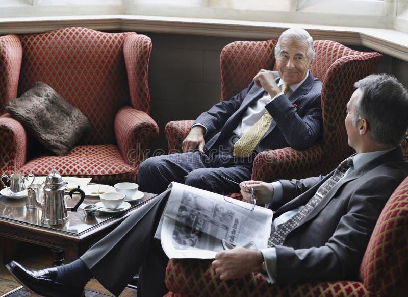 Dois homens de negócios que comunicam-se na entrada imagens de stock royalty free
