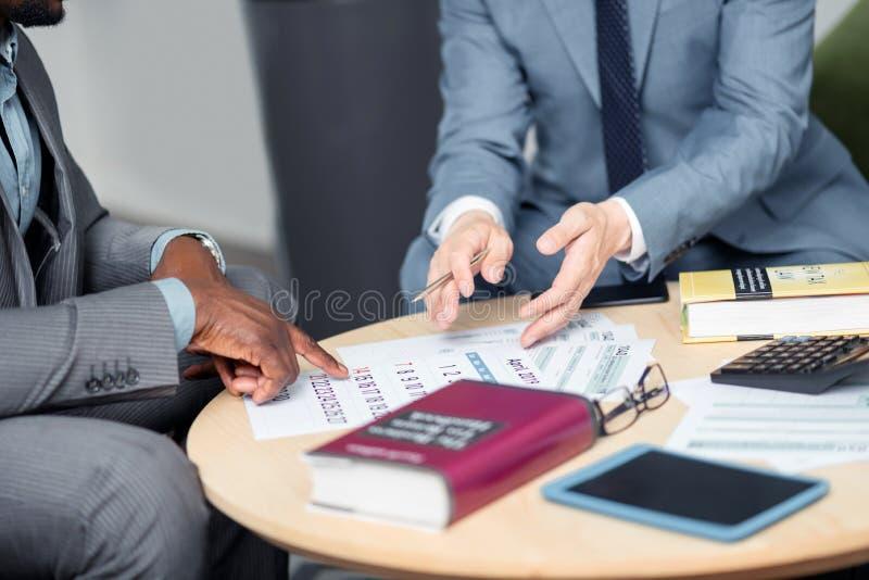 Dois homens de negócios que discutem a negociação seguinte perto do calendário imagem de stock royalty free