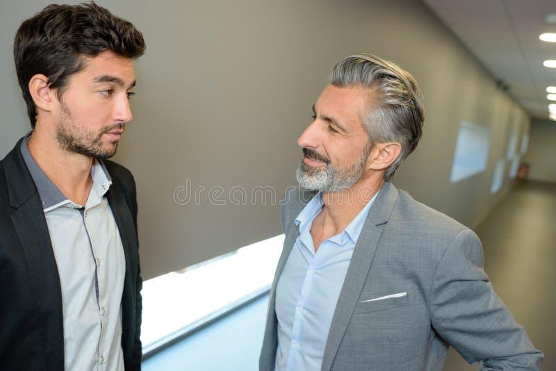 Dois homens de negócios que falam no acorridor imagens de stock royalty free
