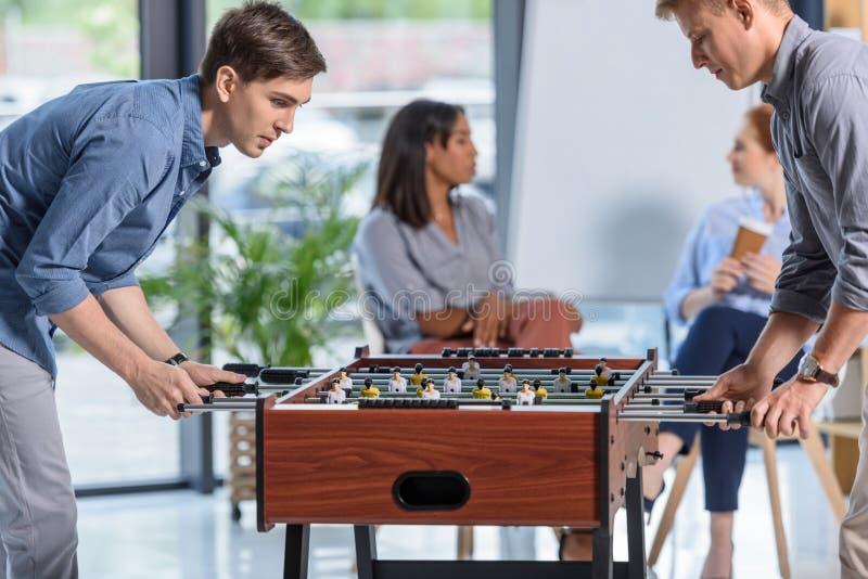 Dois homens de negócios que jogam o futebol da tabela quando mulheres de negócios novas que conversam durante a ruptura foto de stock