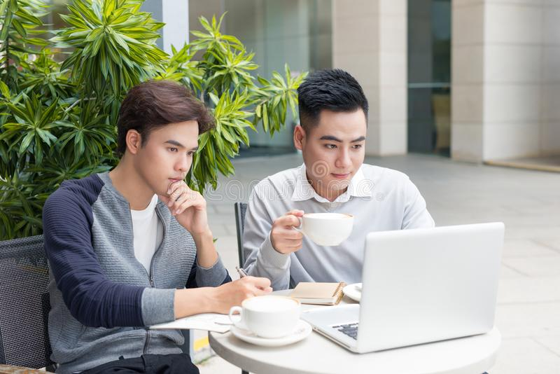 Dois homens de negócios que riem ao ter uma reunião em um cof clássico imagem de stock