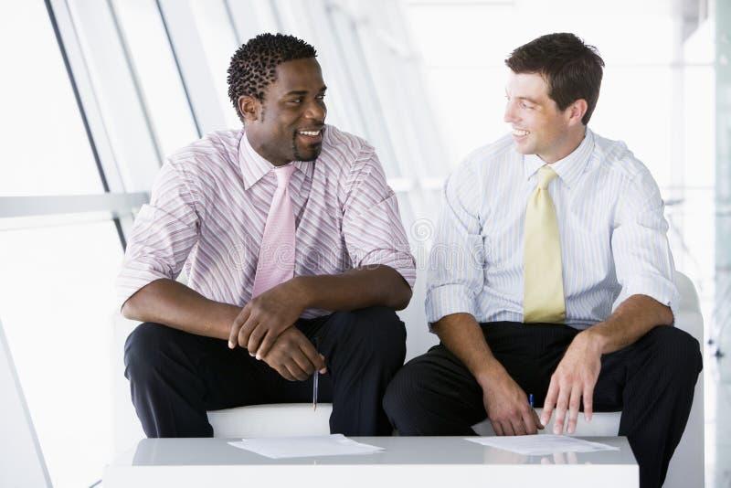 Dois homens de negócios que sentam-se na fala da entrada do escritório