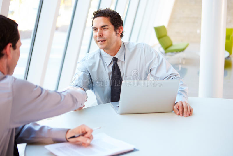 Dois homens de negócios que têm a reunião em torno da tabela no escritório moderno