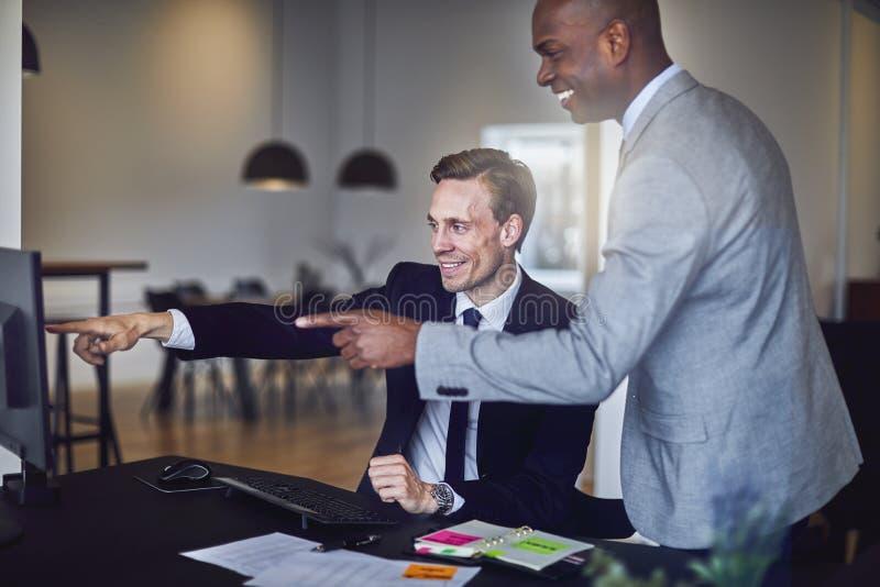 Dois homens de negócios de riso que apontam em um monitor em um escritório foto de stock royalty free