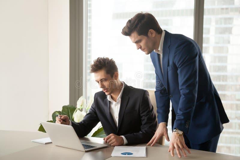 Dois homens de negócios sérios que olham a tela do portátil, trabalhando em pro foto de stock