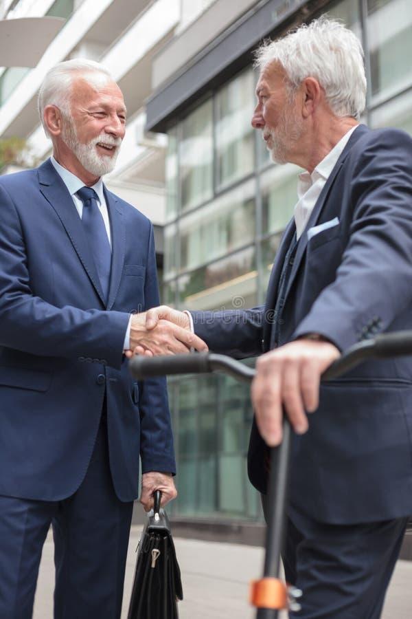 Dois homens de negócios superiores felizes que agitam as mãos, estando na frente de um prédio de escritórios imagem de stock royalty free