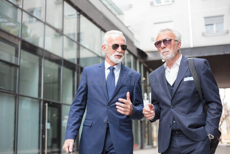 Dois homens de negócios superiores que andam abaixo da rua, discutindo fotografia de stock