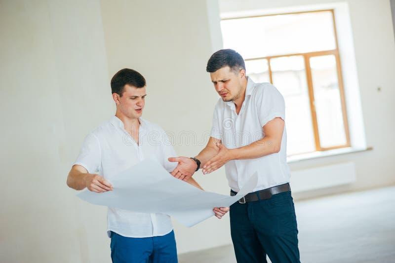 Dois homens de neg?cio ou engeners que trabalham e que discutem o desenho plano da casa durante a constru??o e o processo do repa imagem de stock