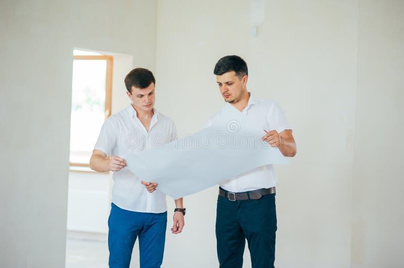 Dois homens de neg?cio ou engeners que trabalham e que discutem o desenho plano da casa durante a constru??o e o processo do repa imagem de stock royalty free