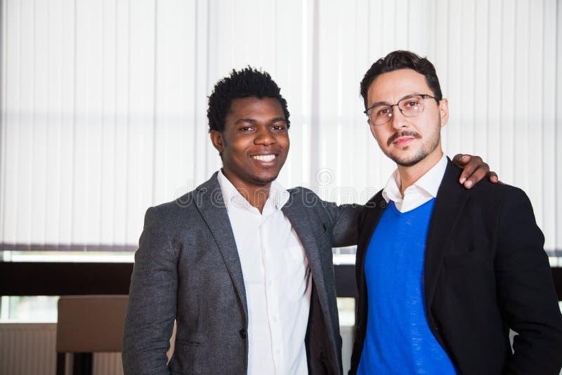 Dois homens de sorriso nos ternos olham a câmera, retrato dos homens de negócios fotografia de stock