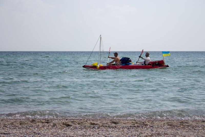 Dois homens desconhecidos no barco de borracha com embarcações e navigação ucraniana da bandeira ao longo do litoral Férias e con foto de stock royalty free
