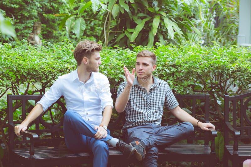 Dois homens dos amigos que falam o assento em um jardim imagem de stock royalty free