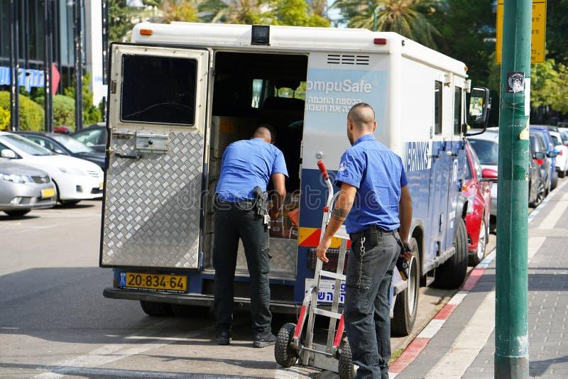 Dois homens dos protetores do caminhão da Empresa de Limiar puseram os sacos do dinheiro no carro protetores que transportam o di imagem de stock