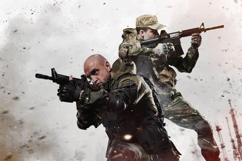 Dois homens dos soldados das forças especiais tomam o alvo na metralhadora imagens de stock