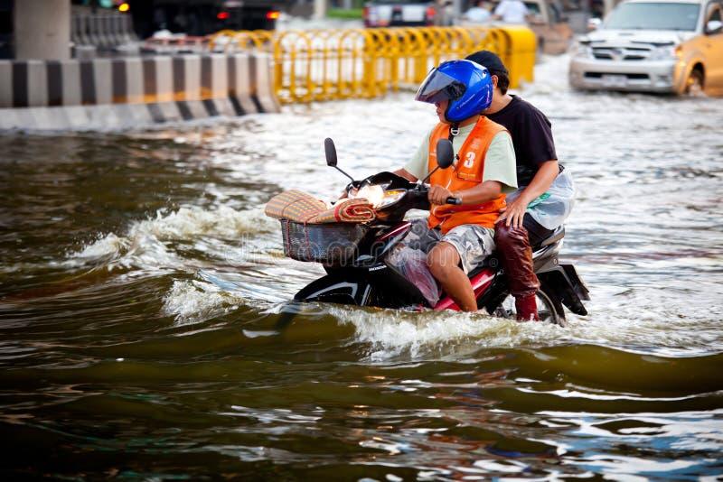 Dois homens em um velomotor através da inundação foto de stock royalty free