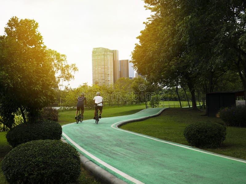 Dois homens estão dando um ciclo em um trajeto da bicicleta em um parque público imagens de stock