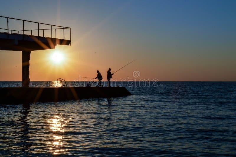 dois homens estão no cais e nos peixes com uma vara de pesca imagens de stock royalty free