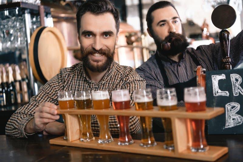 Dois homens farpados testam a cerveja de estilos diferentes em demonstradores da cerveja na cervejaria da cerveja do ofício imagens de stock royalty free