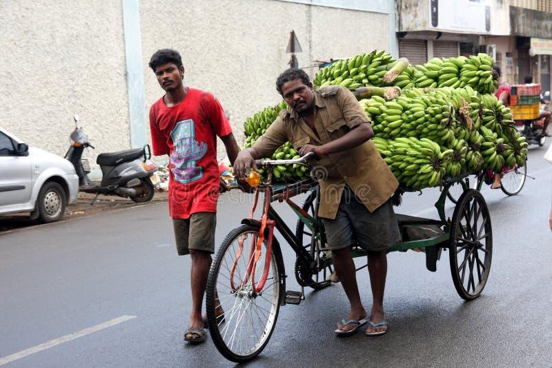 Dois homens indianos estão ajudando a transportar um caminhão da banana na estrada na cidade de Pondicherry fotos de stock royalty free