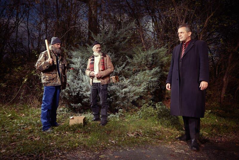 Dois homens mais idosos desabrigados encontraram o homem do gerente no terno no parque do inverno imagem de stock royalty free