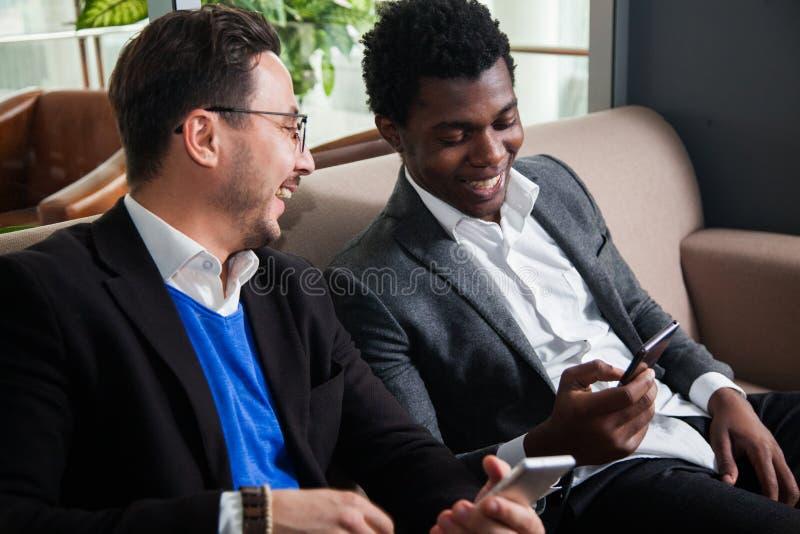 Dois homens multiculturais sentam-se em telefones celulares do sofá, do sorriso e da posse fotos de stock