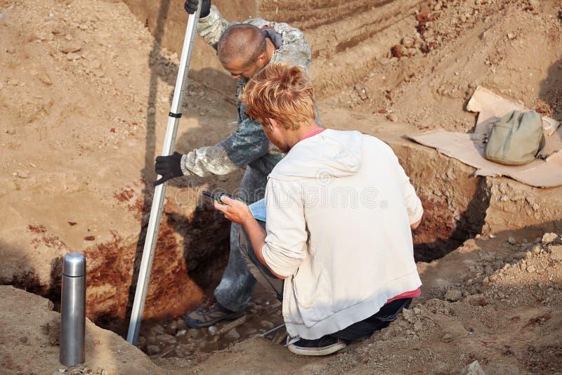 Dois homens no trabalho fora, no processo do escavador Escavações Archaeological imagens de stock