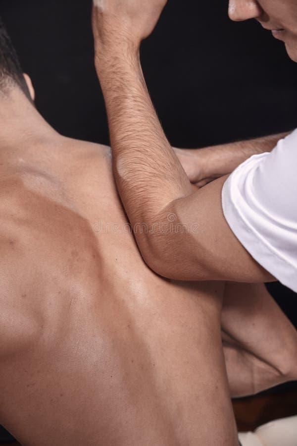 Dois homens novos, 20-29 anos velhos fisioterapeuta que faz massagens os pacientes musculares para tr?s com seu cotovelo, vista t fotografia de stock