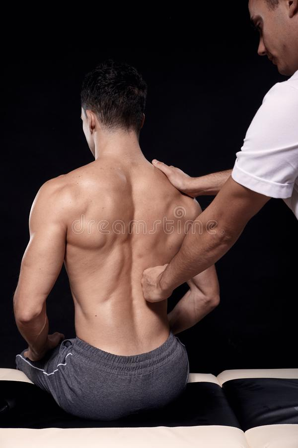 Dois homens novos, 20-29 anos velhos fisioterapeuta que faz massagens os pacientes musculares para tr?s com seu punho, vista tras imagens de stock royalty free