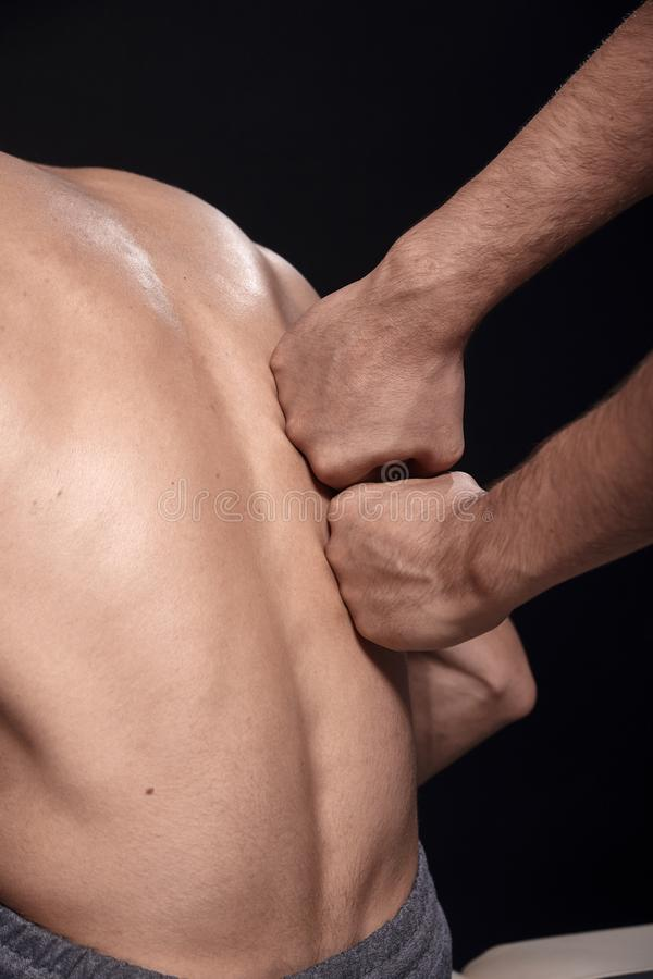 Dois homens novos, 20-29 anos velhos fisioterapeuta que faz massagens os pacientes musculares para tr?s com seus punhos, vista tr imagem de stock royalty free