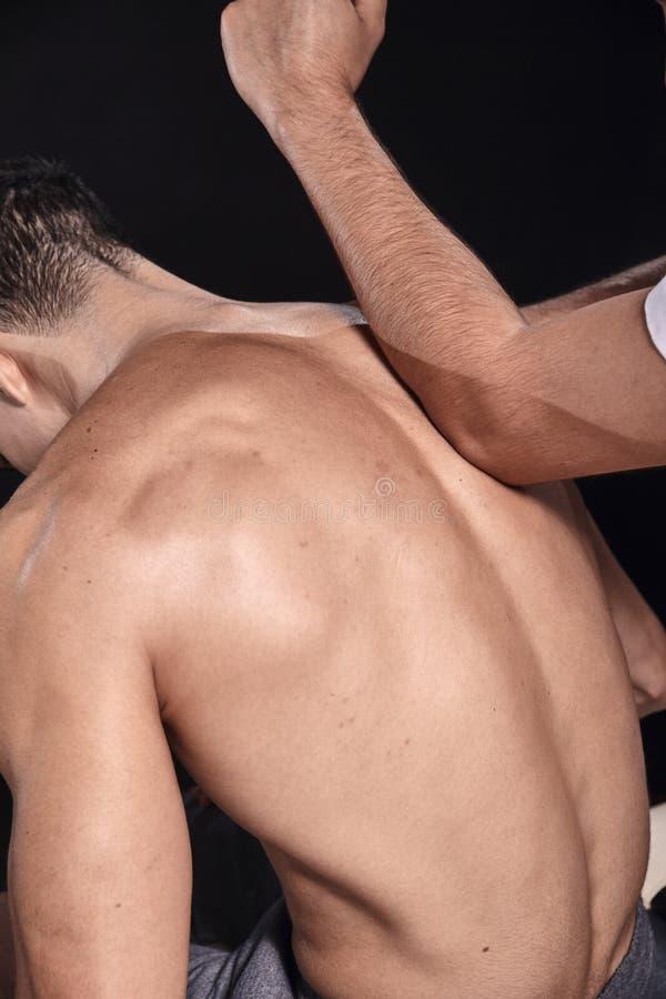 Dois homens novos, 20-29 anos velhos fisioterapeuta que faz massagens os pacientes musculares para tr?s com seu cotovelo, vista t imagem de stock royalty free