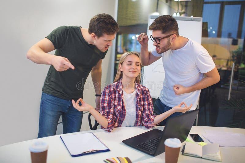 Dois homens novos irritados estão em cima do modelo e do ponto louros nela Gritam Três pessoas estão em uma sala Modelo louro imagens de stock