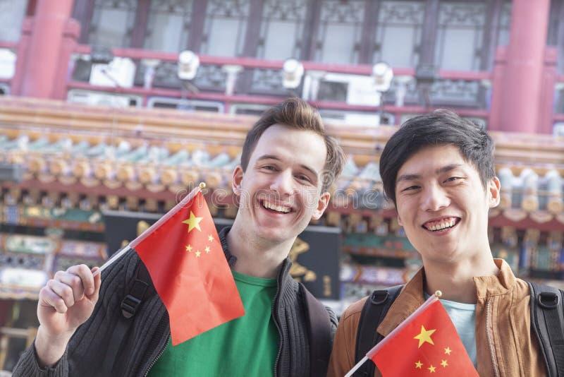 Dois homens novos que guardam bandeiras chinesas. fotos de stock