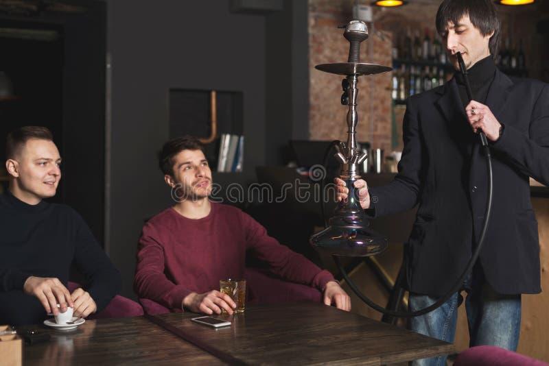 Dois homens novos que pedem o cachimbo de água no café imagem de stock royalty free