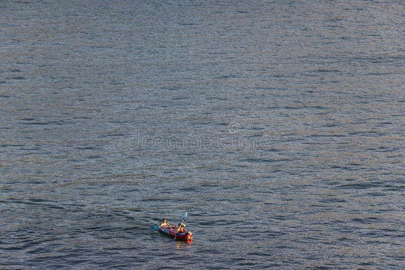 Dois homens novos que remam em um caiaque no mar imagem de stock royalty free