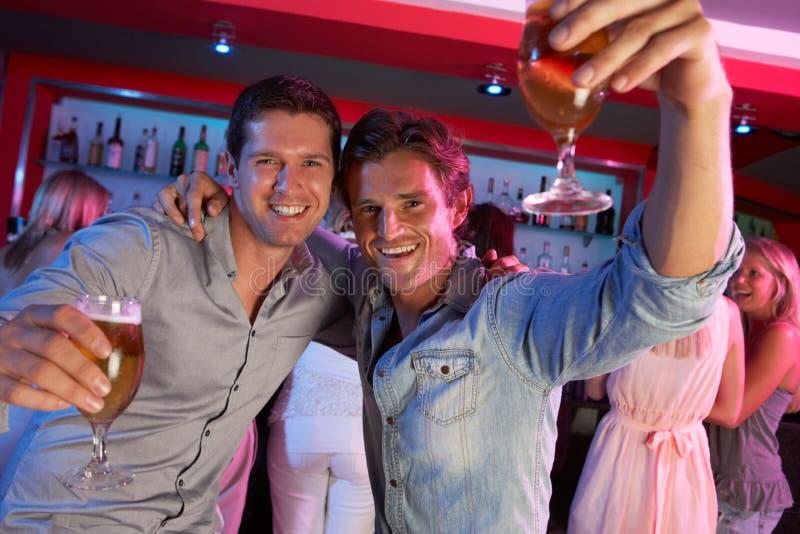Dois homens novos que têm o divertimento na barra ocupada imagens de stock royalty free