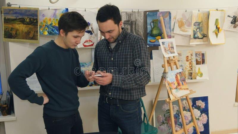 Dois homens novos que usam o smartphone na classe de arte fotografia de stock royalty free