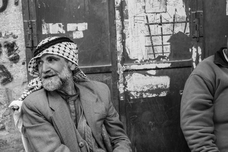 Dois homens palestinos estão sentando-se tendo um bate-papo zigarettes em t foto de stock royalty free