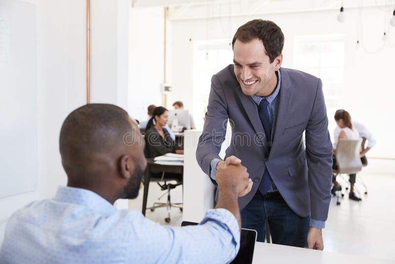 Dois homens que agitam as mãos em uma reunião em um escritório de plano aberto imagem de stock royalty free