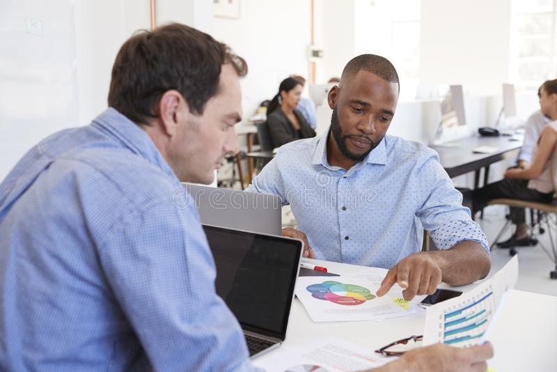 Dois homens que discutem originais em um escritório ocupado imagens de stock royalty free