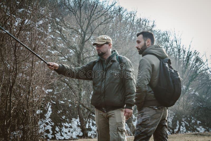 Dois homens que falam na natureza e levam trouxas e varas de pesca foto de stock