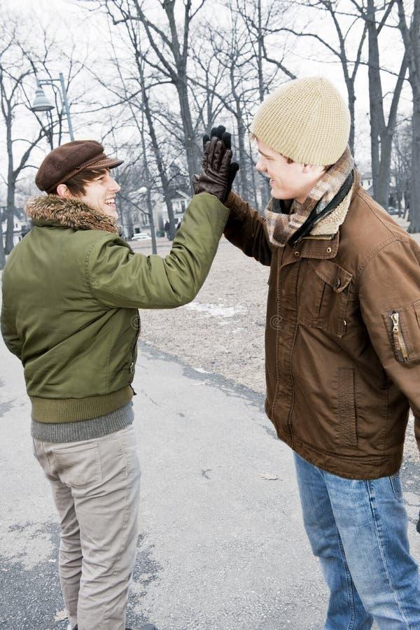 Dois homens que fazem a elevação cinco no parque foto de stock