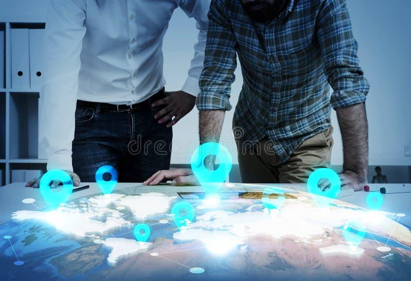 Dois homens que inclinam-se acima do mapa do mundo com marcos fotos de stock