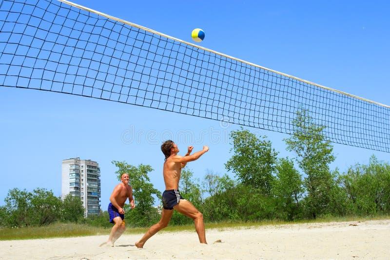 Dois homens que jogam o voleibol de praia fotos de stock royalty free