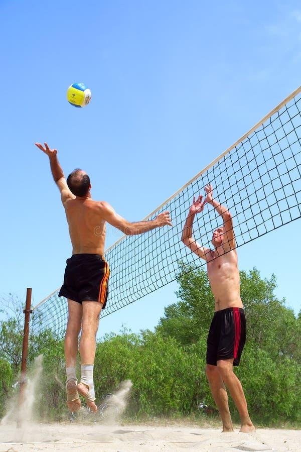 Dois homens que jogam o voleibol de praia - o homem calvo curto ganha sobre t foto de stock royalty free
