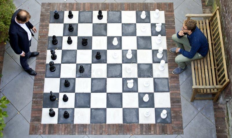 Dois homens que jogam um jogo da xadrez exterior foto de stock royalty free