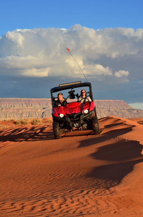 Dois homens que montam uns quatro Wheeler Through Beautiful Sand imagem de stock
