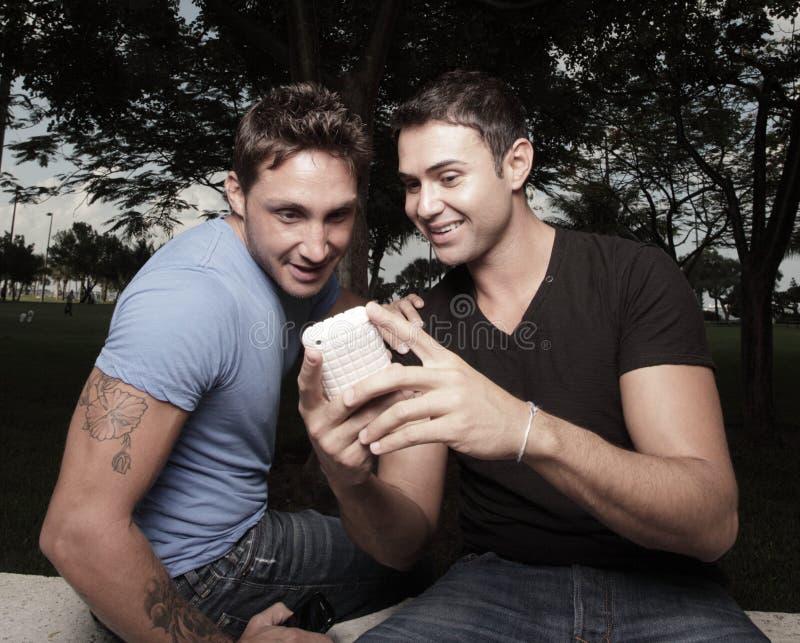 Dois homens que olham um telefone fotos de stock