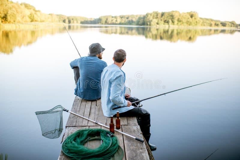 Dois homens que pescam no lago foto de stock royalty free