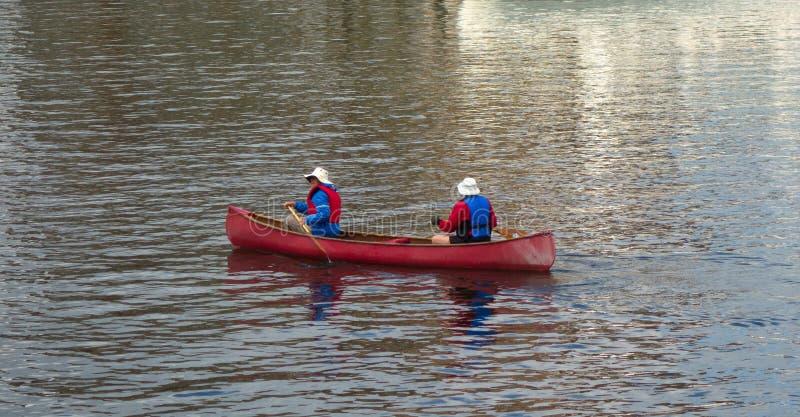 Dois homens que remam uma canoa no Oceano Pacífico no verão foto de stock