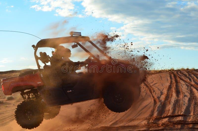 Dois homens que saltam uns quatro Wheeler Over uma duna de areia imagens de stock